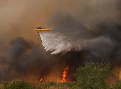 A helicopter drops water on a fire near the entrance to The Cliffs on the south east side Possum Kingdom Lake, Texas on Tuesday, August 30.