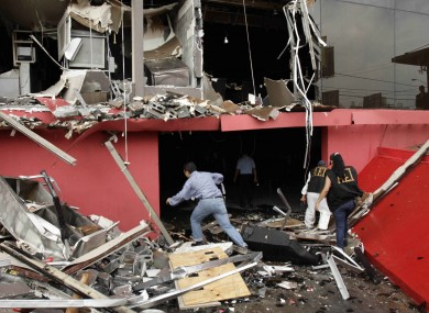 Investigators walk through debris of the charred Casino Royale after a deadly arson assault, in Monterrey, Mexico