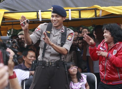 police officer Norman Kamaru, center, dances with a fan during a show in Jakarta at the height of his fame earlier this year