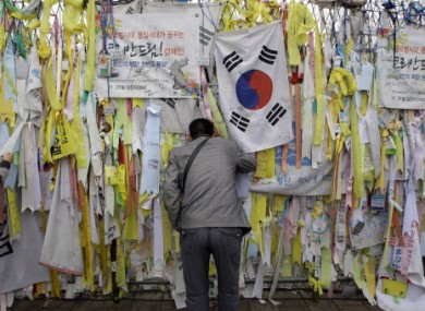 A man looks at the North side through the barbed wire fence decorated with messages wishing for the reunification of the Koreas near the border village of Panmunjom.