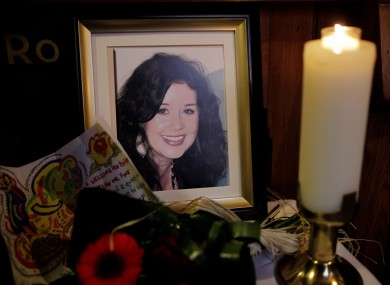 A candle burns during a Memorial Mass for murdered Irish woman Jill Meagher (seen in framed photo) at St Peter's Church, Drogheda, Co Louth