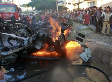 People look at a wreckage of the car in which Ahmed Jabari, head of the Hamas military wing in Gaza City, was killed.