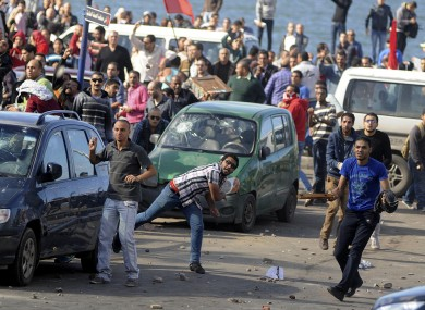 Protesters hurl stones during clashes between supporters and opponents of President Mohammed Morsi in Alexandria, Egypt,