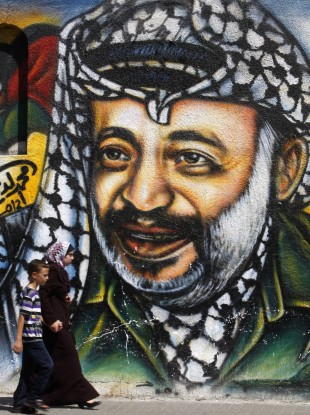 Palestinians pass by a mural depicting late Palestinian President Yasser Arafat, in Gaza City