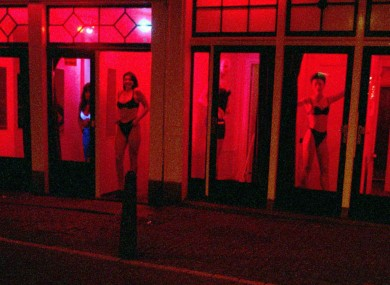 FILE-Prostitutes stand behind red-lit windows, waiting for customers in Amsterdam's Red Light district