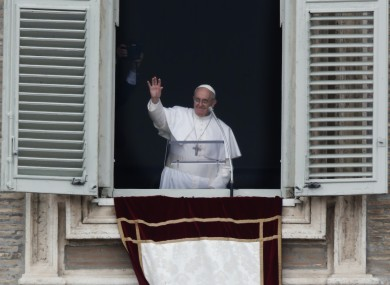 Pope Francis waves to the crowd in St Peter's Square after saying the Angelus this morning