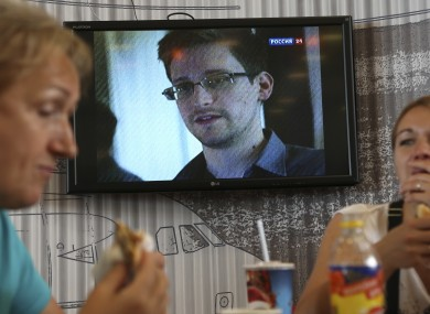 Wednesday, June 26, 2013 file photo transit passengers eat at a cafe with a TV screen with a news program showing a report on Edward Snowden