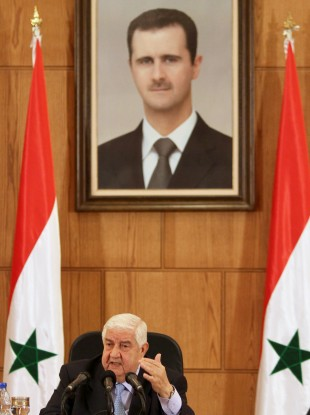 Syrian Foreign Minister Walid al-Moallem speaks during a press conference beneath a portrait of President Bashar Assad in Damascus today.