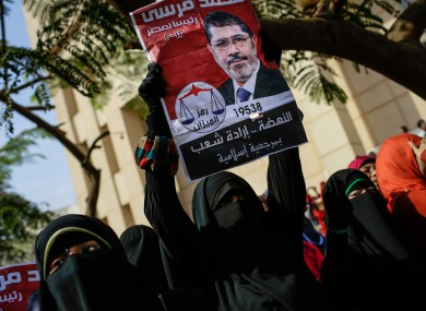 A Morsi supporter holds an old presidential campaign poster during a protest yesterday.