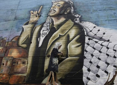 Palestinian Hanadi Kharma paints a mural of Yasser Arafat in the West Bank city of Nablus yesterday.