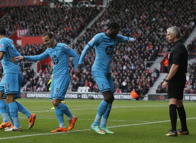 Referee Chris Foy watches Adebayor celebrate his second goal.