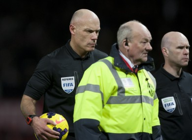 Referee Howard Webb, left, walks from the pitch after Manchester United's 2-1 loss to Tottenham