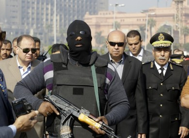 An Egyptian masked policeman guards Cairo's state security chief, Osama al-Saghir, third right, as he visits Tahrir Square.
