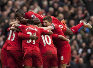 Liverpool's Daniel Sturridge, unseen, is swamped by jubilant teammates as he celebrates scoring his team's fourth goal.