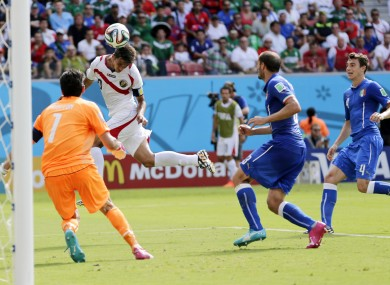 Costa Rica's Bryan Ruiz heads the ball to score his side's first goal over Italy's goalkeeper Gianluigi Buffon.